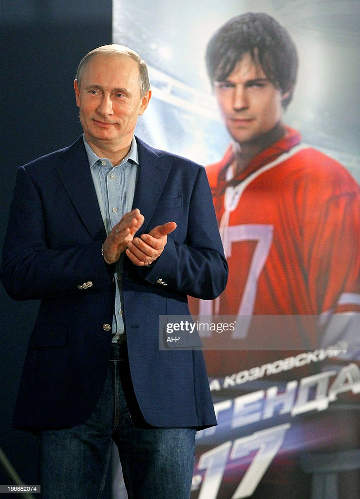 Russia's President Vladimir Putin applauds after watching the movie ' Legend No. 17' at Primorsky sanatorium movie theater outside the Black Sea resort of Sochi, on April 17, 2013, with the film poster depicting actor Danila Kozlovsky, who plays the leading role of Soviet ice hockey legend Valeri Kharlamov, displayed in the background. AFP PHOTO/ RIA-NOVOSTI/ POOL / MIKHAIL KLIMENTYEV