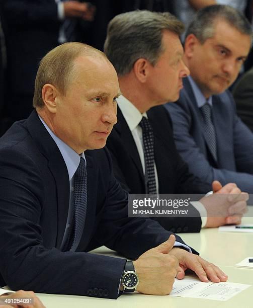 Russia's President Vladimir Putin Crimea's prime minister Sergei Aksyonov and Putin's Envoy to Crimea Oleg Belaventsev attend a meeting with the...