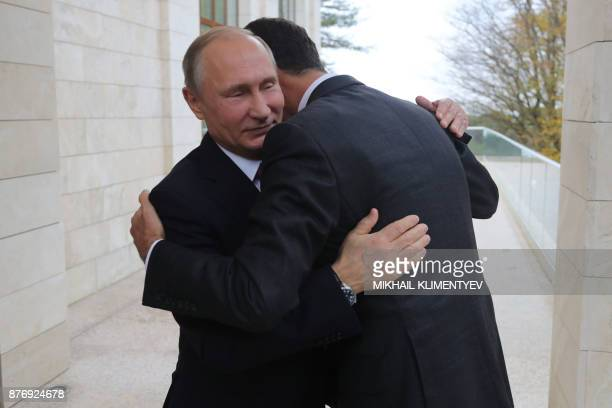 TOPSHOT Russia's President Vladimir Putin embraces his Syrian counterpart Bashar alAssad during a meeting in Sochi on November 20 2017 / AFP PHOTO /...