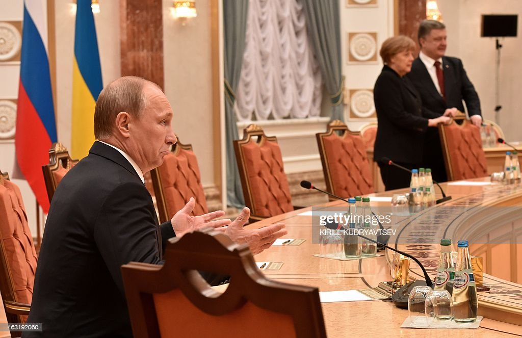 Russia's President Vladimir Putin gestures as German Chancellor Angela Merkel and Ukraine's President Petro Poroshenko stand nearby during a meeting...