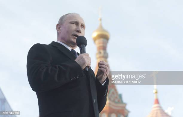 Russia's President Vladimir Putin gives a speech during a rally and a concert by the Kremlin Wall in central Moscow on March 18 to mark one year...