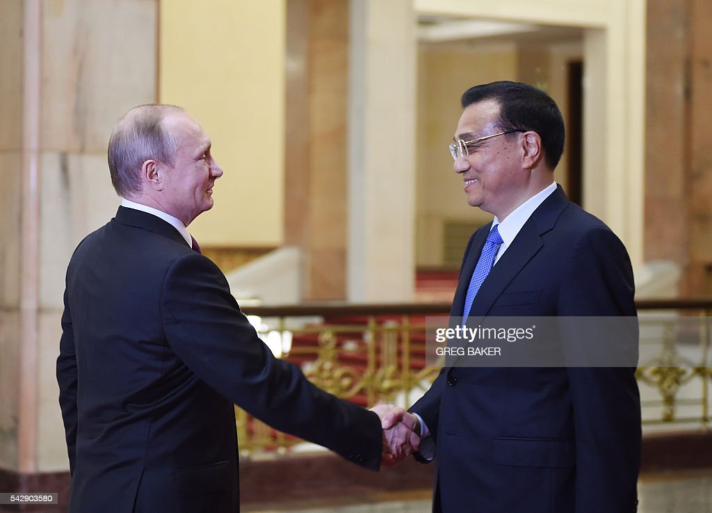 Russia's President Vladimir Putin (L) is greeted by Chinese Premier Li Keqiang at the Great Hall of the People in Beijing on June 25, 2016. / AFP / POOL / GREG