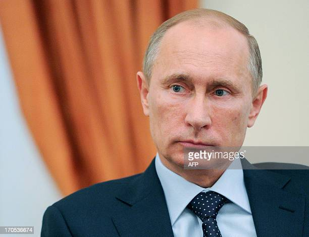 Russia's President Vladimir Putin looks on during a meeting with Civil 20 representatives in NovoOgaryovo residence outside Moscow on June 14 2013...