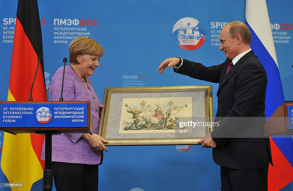 Russia's President Vladimir Putin (R) presents Germany's Chancellor Angela Merkel an old lithograph dedicated to the signing of a Russian-German trade agreement in 1894 at a press conference during an International Economic Forum in St. Petersburg, on June 21, 2013. Putin and Merkel announced today that they would both attend the opening of a Saint Petersburg exhibition including treasures taken by the Red Army at the end of World War II. German officials had said earlier their visit to the 'Bronze Age of Europe -- Europe Without Borders' exhibition at the Hermitage museum had been scrapped due to what German media said was a wrangle over the future of the so-called trophy art. MALTSEVA