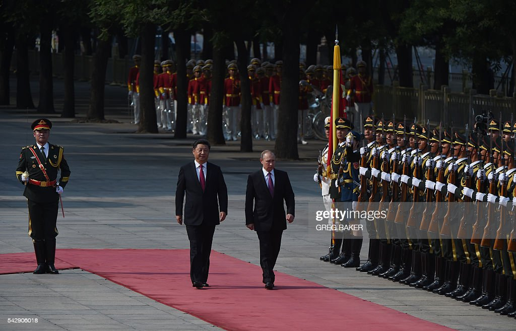 Russia's President Vladimir Putin (centre R) reviews an honour guard with Chinese President Xi Jinping (centre L) during a welcoming ceremony in Beijing on June 25, 2016. Putin is on a state visit to China. / AFP / GREG