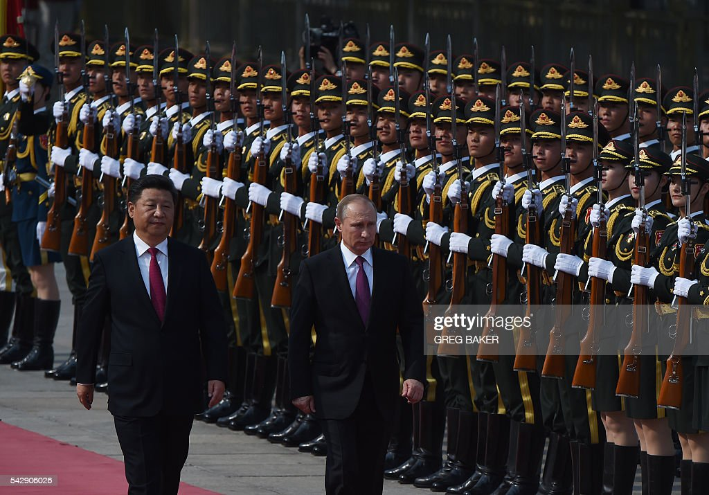 Russia's President Vladimir Putin (C) reviews an honour guard with Chinese President Xi Jinping (L) during a welcoming ceremony in Beijing on June 25, 2016. Putin is on a state visit to China. / AFP / GREG