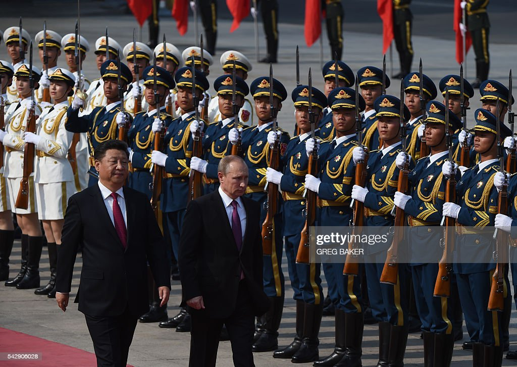 Russia's President Vladimir Putin (2nd L) reviews an honour guard with Chinese President Xi Jinping (L) during a welcoming ceremony in Beijing on June 25, 2016. Putin is on a state visit to China. / AFP / GREG