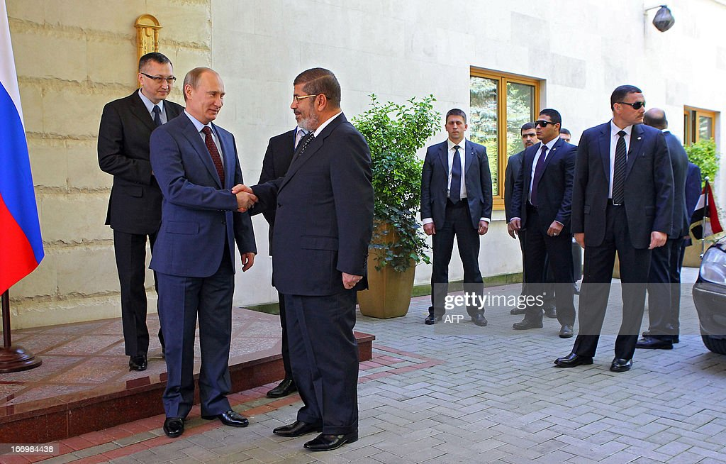 Russia's President Vladimir Putin (2nd L) shakes hands with his Egyptian counterpart Mohamed Mursi during their meeting in the Black Sea resort of Sochi, on April 19, 2013.