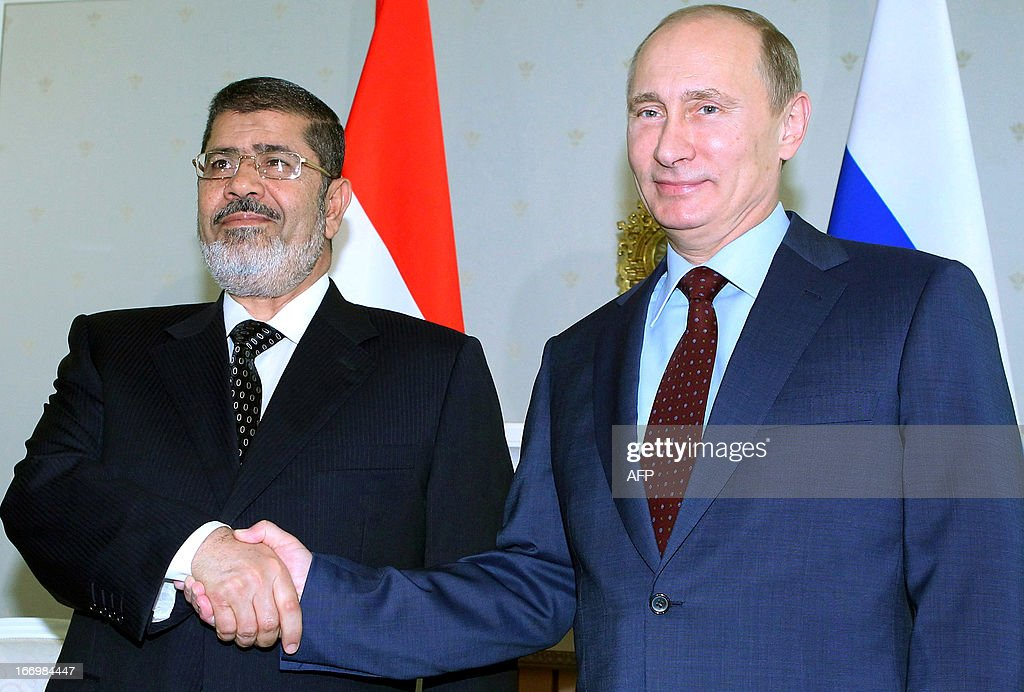 Russia's President Vladimir Putin (R) shakes hands with his Egyptian counterpart Mohamed Mursi during their meeting in the Black Sea resort of Sochi, on April 19, 2013.