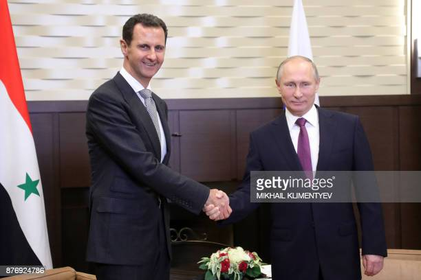 TOPSHOT Russia's President Vladimir Putin shakes hands with his Syrian counterpart Bashar alAssad during a meeting in Sochi on November 20 2017 / AFP...