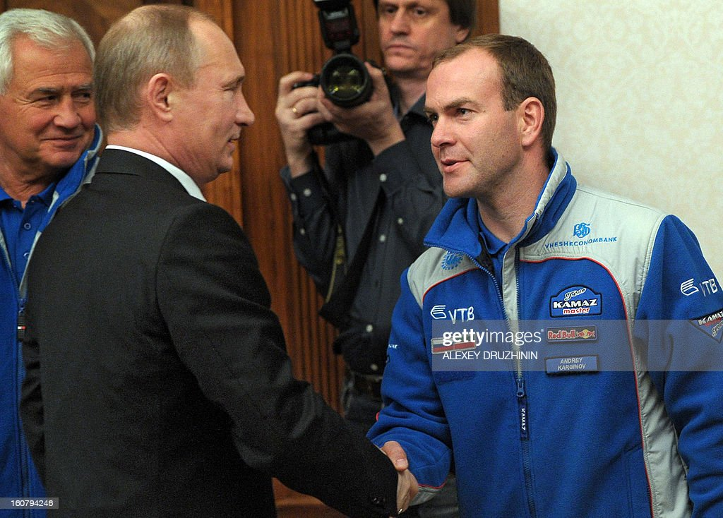 Russia's President Vladimir Putin (2nd L) shakes hands with Kamaz-master racing team's pilot Andrey Karginov (R) as he meets Russian winners of Dakar 2013 truck rally in his residence in the Black Sea resort of Sochi, on February 5, 2013, with Kamaz-master's head Semyon Yakubov (L) attending .