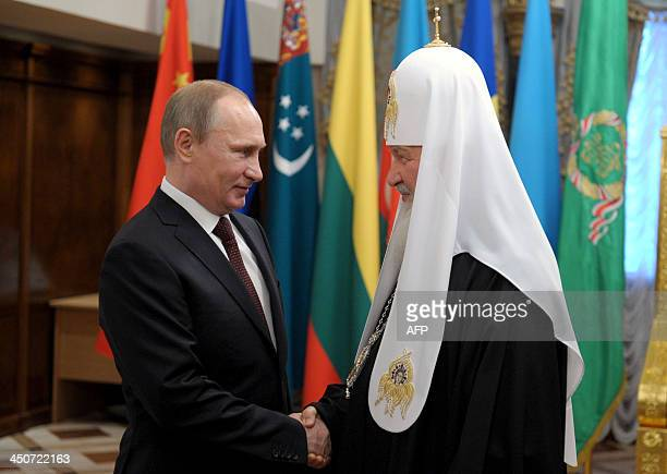 Russia's President Vladimir Putin shakes hands with Russian Orthodox Church head Patriarch Kirill as they meet in Christ the Saviour Cathedral in...