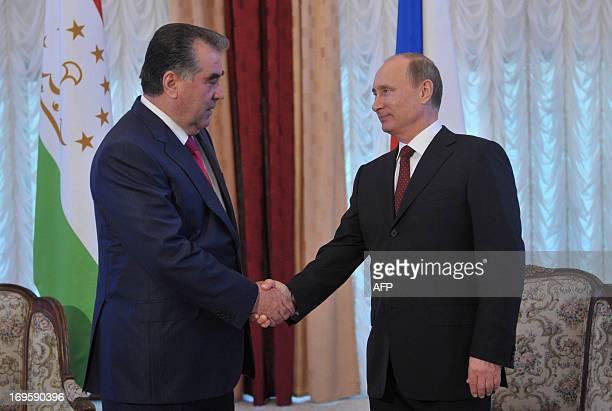 Russia's President Vladimir Putin shakes hands with Tajik President Emomali Rakhmon as they meet on the sidelines of an informal summit of the...