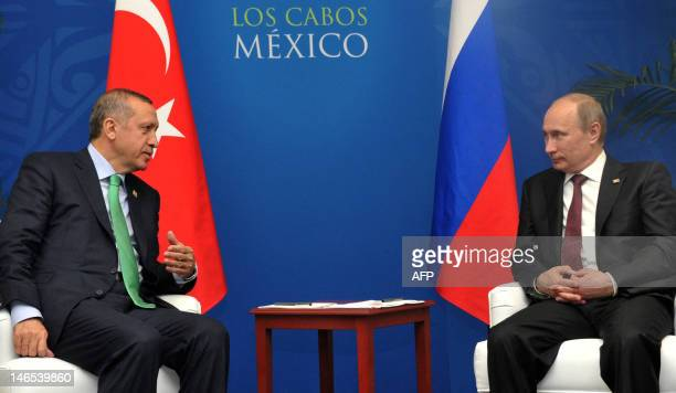 Russia's President Vladimir Putin shakes hands with Turkish Prime Minister Recep Tayyip Erdogan as they meet on the sidelines of the Group of 20...