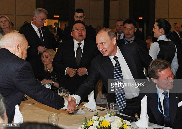 Russia's President Vladimir Putin shaking hands while attending the International Olympic Committee Presidents Gala Dinner in Sochi on February 6 on...