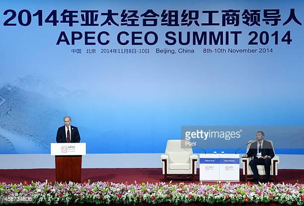 Russia's President Vladimir Putin speaks as Oleg Deripaska CEO of UC Rusal looks on at the APEC CEO Summit as part of the AsiaPacific Economic...
