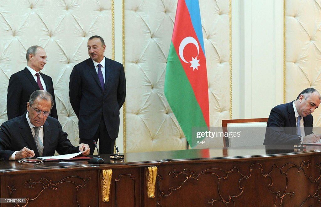 Russia's President Vladimir Putin (back L) speaks with his Azerbaijani counterpart Ilham Aliyev (back 2nd L) during a signing ceremony in Baku, on August 13, 2013, with Russian Foreign Minister Sergei Lavrov (front L) and his Azerbaijani counterpart Elmar Mammadyarov (R) signing an agreement. Russian crude giant Rosneft signed yesterday an oil and gas agreement with Azerbaijan's state energy firm aimed at loosening the European Union's ties with the key Caspian market. Neither side disclosed the full details of a deal that was sealed on the sidelines of talks in Baku between Putin and Aliyev. AFP PHOTO/ RIA-NOVOSTI/ POOL/ MIKHAIL KLIMENTYEV