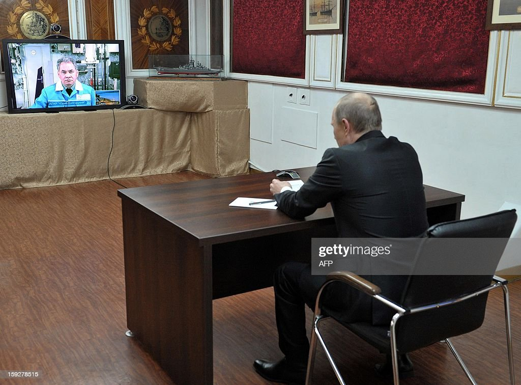Russia's President Vladimir Putin speaks with Russian Defense Minister Sergei Shoigu seen on a screen during on a video conference on board a navy ship at the Barents Sea Russian naval base of Severomorsk, late on January 10, 2013. Putin visited the base of Russia's Northern Fleet to commission the massive but extremely late-in-construction Yuri Dolgoruky nuclear submarine.