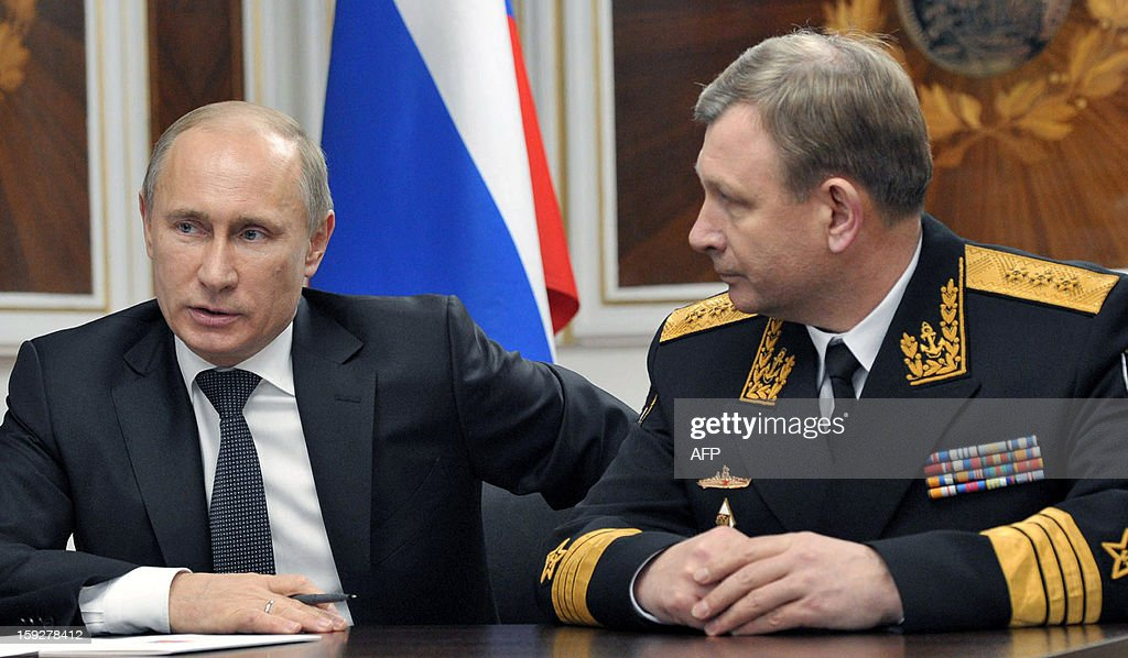 Russia's President Vladimir Putin (L) speaks with Russian Navy's commander-in-chief Viktor Chirkov on board a navy ship at the Barents Sea Russian naval base of Severomorsk, late on January 10, 2013. Putin visited the base of Russia's Northern Fleet to commission the massive but extremely late-in-construction Yuri Dolgoruky nuclear submarine.