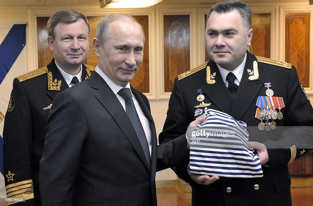 Russia's President Vladimir Putin (2nd L) speaks with Russian Navy's commander-in-chief Viktor Chirkov (L) and the captain of the Peter the Great nuclear cruiser, Vladislav Malakhovsky (R), on board a navy ship at the Barents Sea Russian naval base of Severomorsk, late on January 10, 2013. Putin visited the base of Russia's Northern Fleet to commission the massive but extremely late-in-construction Yuri Dolgoruky nuclear submarine.