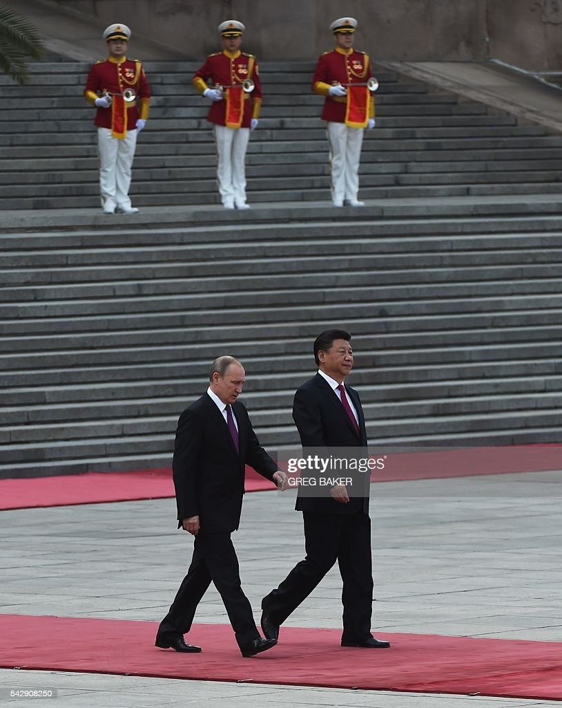 Russia's President Vladimir Putin (L) walks with Chinese President Xi Jinping during a welcoming ceremony in Beijing on June 25, 2016. Putin is on a state visit to China. / AFP / GREG
