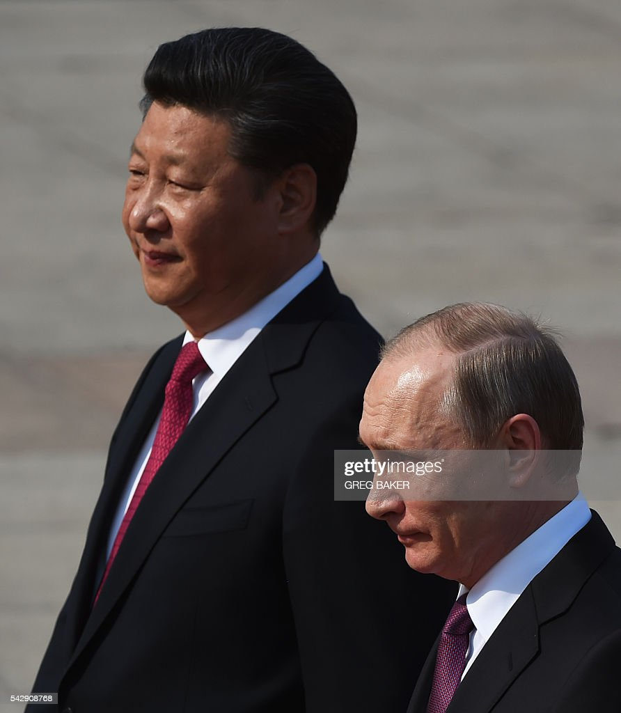 Russia's President Vladimir Putin (R) walks with Chinese President Xi Jinping during a welcoming ceremony in Beijing on June 25, 2016. Putin is on a state visit to China. / AFP / GREG