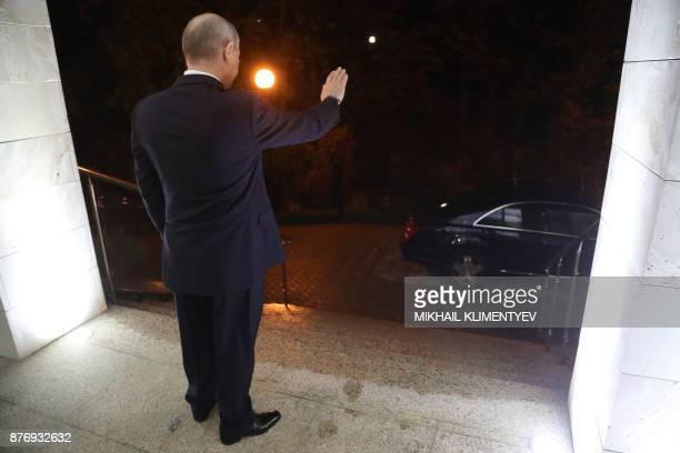 TOPSHOT Russia's President Vladimir Putin waves his hand as his Syrian counterpart leaves after a meeting in Sochi on November 20 2017 Russian...