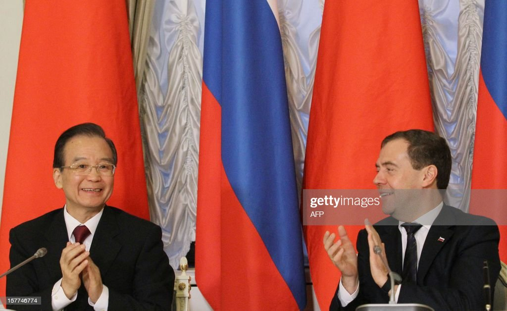Russia's Prime Minister Dmitry Medvedev (R) and China's Prime Minister Wen Jiabao applaud during a joint press conference after their meeting in Moscow, on December 6, 2012. Wen Jiabao is on a visit to Russia.