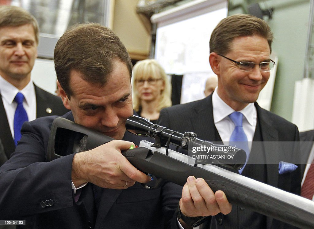 Russia's Prime Minister Dmitry Medvedev (L) and Finnish Prime Minister Jyrki Katainen (R) look at rifles during their visit to the Aalto University in Helsinki, late on Noveber 14, 2012.