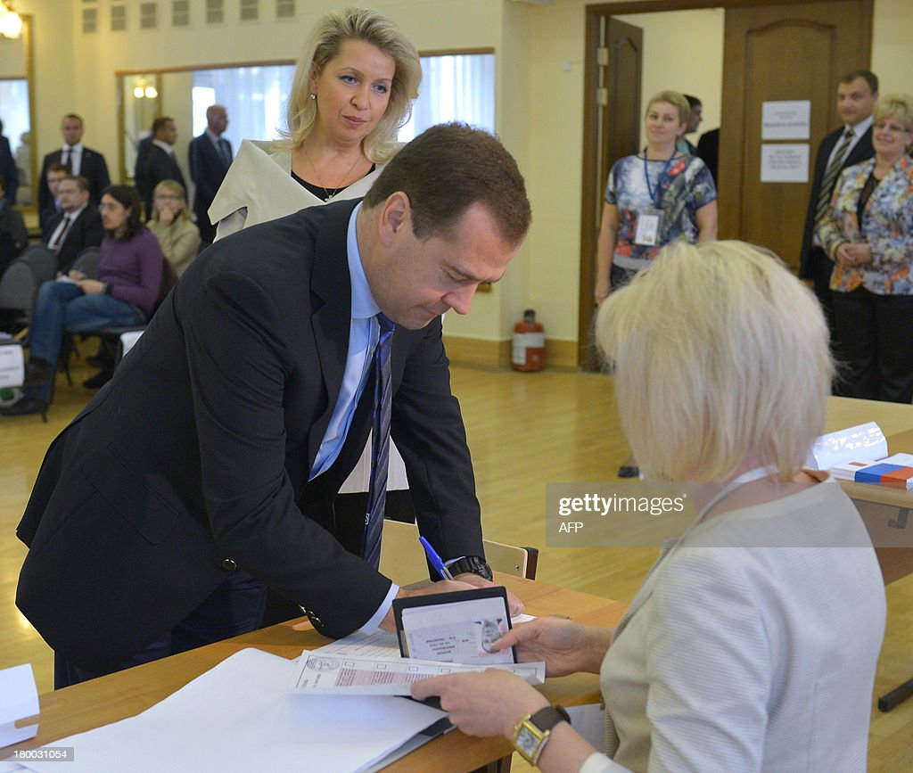 Russia's Prime Minister Dmitry Medvedev gets his ballot at a polling station during a mayoral election in Moscow, on September 8, 2013, with Medvedev's wife, Svetlana (back), attending. Top critic of President Vladimir Putin, Alexei Navalny, faced today a Kremlin-backed Sergei Sobyanin in a hotly contested Moscow mayoral poll, the first time an opposition leader has been allowed to stand in a high-profile election. AFP PHOTO / RIA-NOVOSTI / POOL / ALEXANDER ASTAFYEV