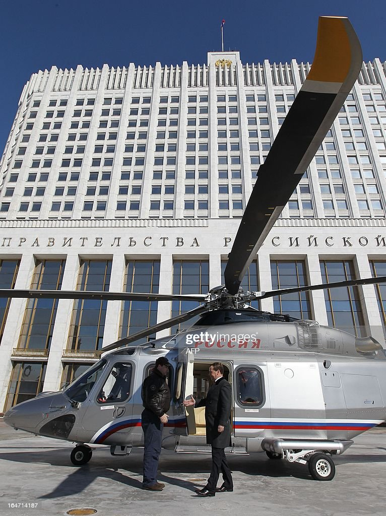 Russia's Prime Minister Dmitry Medvedev (R) gets out from a helicopter at a pad just outside the government headquarters in Moscow, on March 27, 2013.