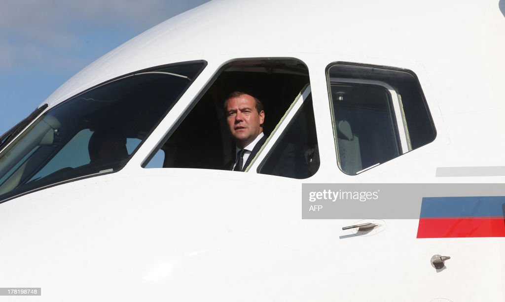 Russia's Prime Minister Dmitry Medvedev is seen inside of the Sukhoi Superjet100 cabin as he observes the flying craft samples at the MAKS...