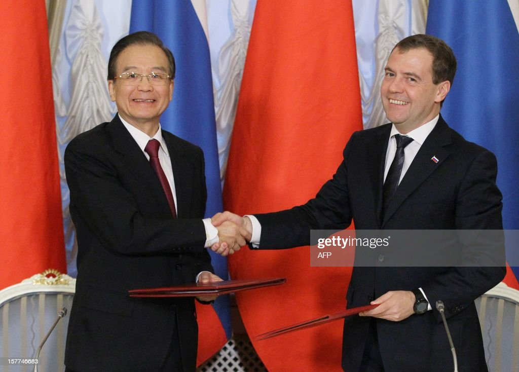 Russia's Prime Minister Dmitry Medvedev (R) shakes hands with China's Prime Minister Wen Jiabao during their meeting in Moscow, on December 6, 2012. Wen Jiabao is on a visit to Russia. AFP PHOTO/ RIA-NOVOSTI/ POOL/ YEKATERINA SHTUKINA