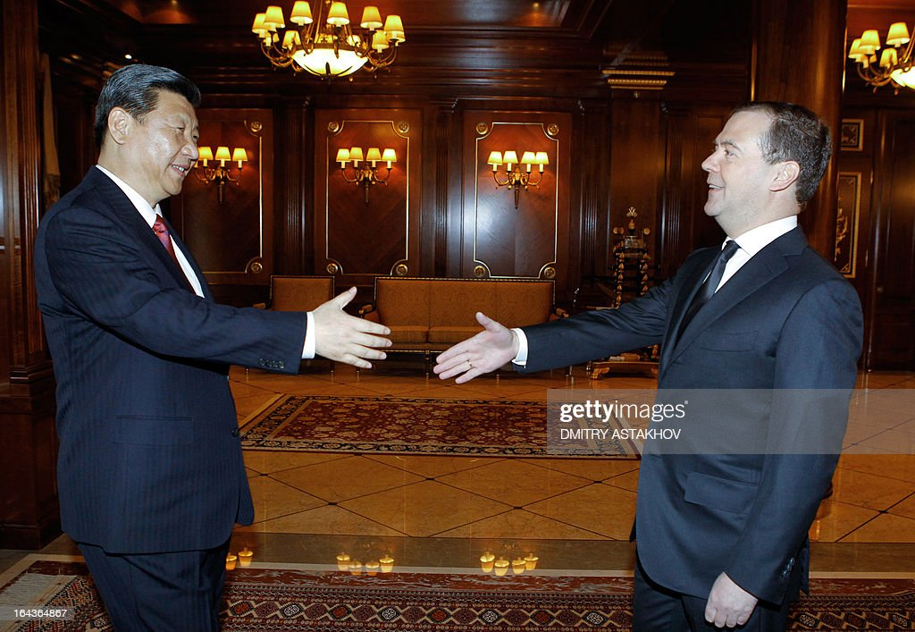 Russia's Prime Minister Dmitry Medvedev (R) shakes hands with China's President Xi Jinping during their meeting in Gorky residence outside Moscow on March 23, 2013. Xi Jinping arrived in Moscow on his first foreign trip, to cement ties between the two countries by inking a raft of energy and investment accords.