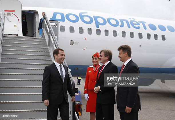 Russia's Prime Minister Dmitry Medvedev speaks with Aeroflot's General Director Vitaly Savelyev and Transport Minister Maxim Sokolov at Moscow's...