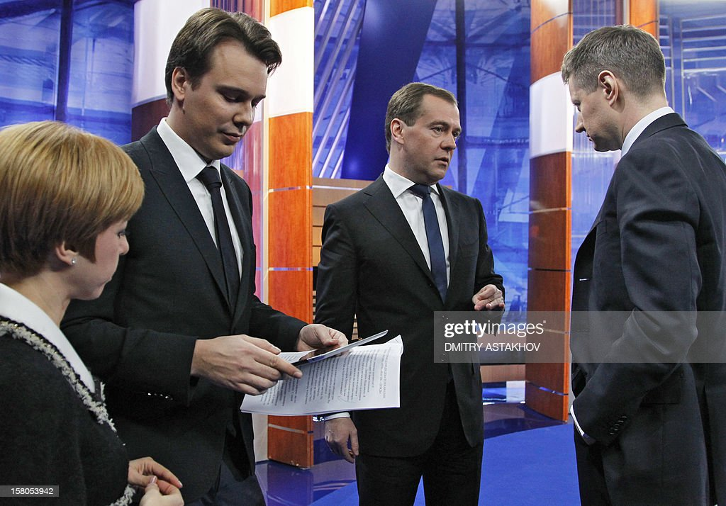 """Russia's Prime Minister Dmitry Medvedev (2nd R) speaks with journalists after recording an interview with major national television channels in Moscow, on December 7, 2012. Stark divisions within Russia's elite were exposed today when a hot mic mishap showed Medvedev during his Friday's off-the-record conversation with journalists slamming security forces as """"jerks"""" for launching an early morning raid against filmmaker Pavel Kostomarov who has been working on an Internet documentary about the Russian opposition called """"Srok"""" (Term)."""