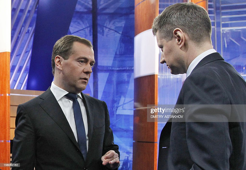 "Russia's Prime Minister Dmitry Medvedev (L) speaks with NTV television newscaster Alexei Pivovarov (R) after recording an interview with major national television channels in Moscow, on December 7, 2012. Stark divisions within Russia's elite were exposed today when a hot mic mishap showed Medvedev during his Friday's off-the-record conversation with Pivovarov slamming security forces as ""jerks"" for launching an early morning raid against filmmaker Pavel Kostomarov who has been working on an Internet documentary about the Russian opposition called ""Srok"" (Term)."