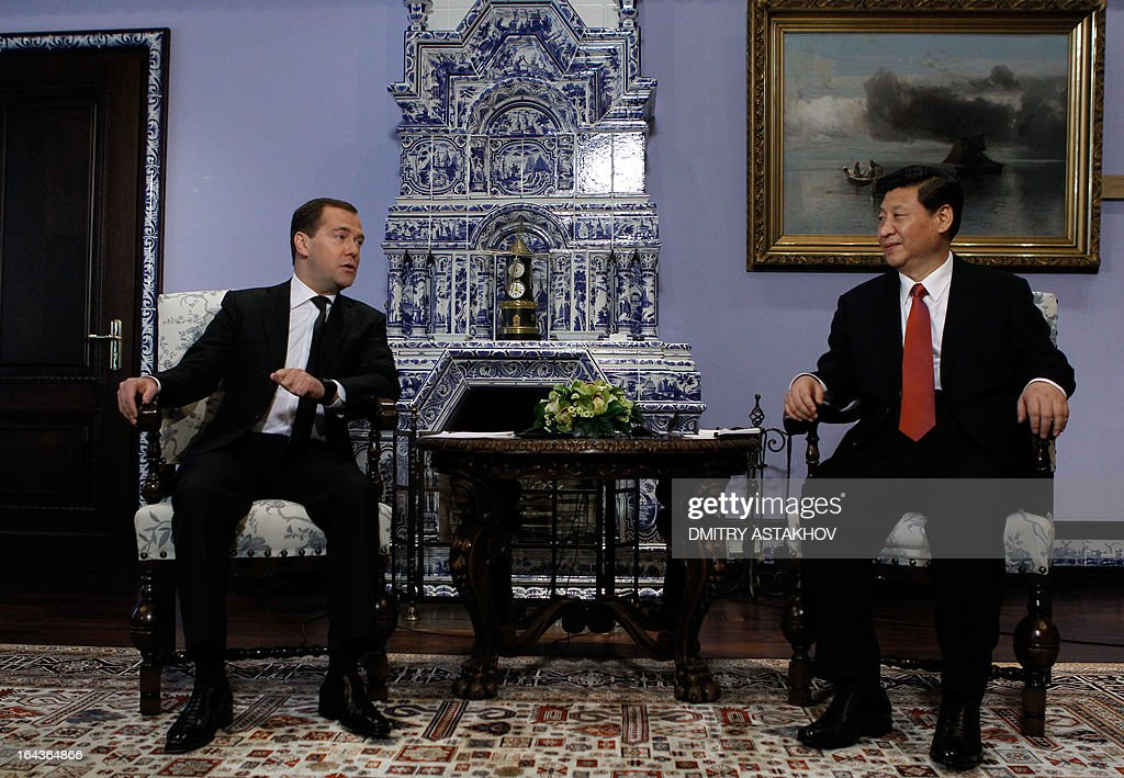Russia's Prime Minister Dmitry Medvedev (L) talks with China's President Xi Jinping during their meeting in Gorky residence outside Moscow on March 23, 2013. Xi Jinping arrived in Moscow on his first foreign trip, to cement ties between the two countries by inking a raft of energy and investment accords.