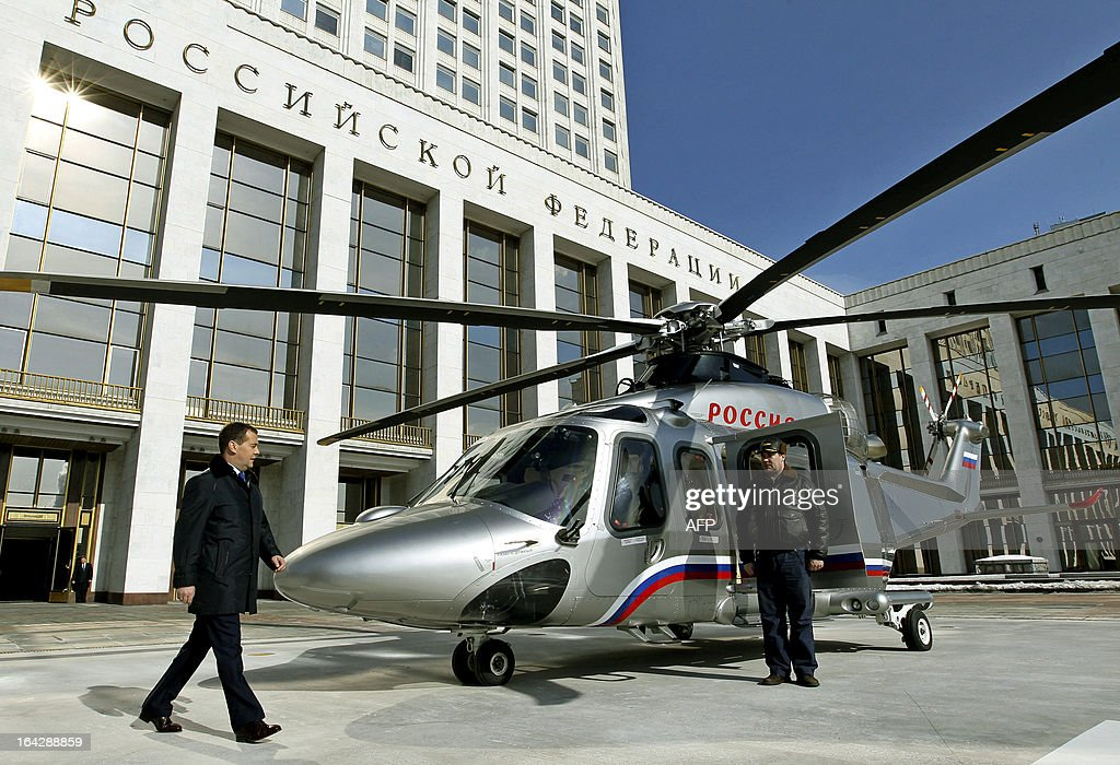 Russia's Prime Minister Dmitry Medvedev (L) walks toward a helicopter at a pad just outside the government headquarters in Moscow, on March 22, 2013.