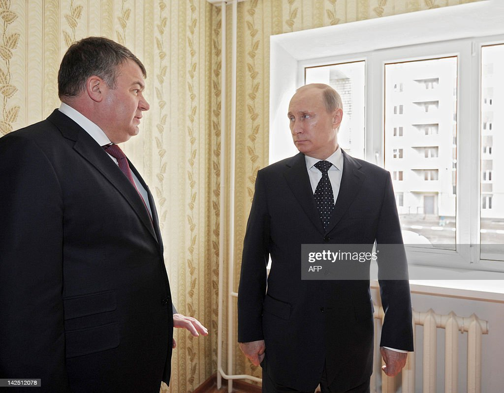 Russia's Prime Minister Vladimir Putin (R) and Defence Minister Anatoly Serdyukov (L) visit one of the apartments in a compound built for military officers in the city of Engels on April 6, 2012.