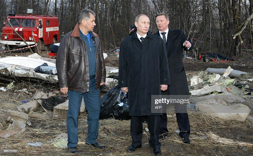 Russia's Prime Minister Vladimir Putin and Emergencies Minister Sergei Shoigu listen to explanation of Deputy Prime Minister Sergei Ivanov during...