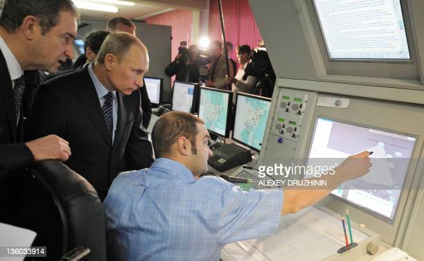 Russia's Prime Minister Vladimir Putin listenes explanations in the air traffic control operations room during a visit to one of the divisions of...
