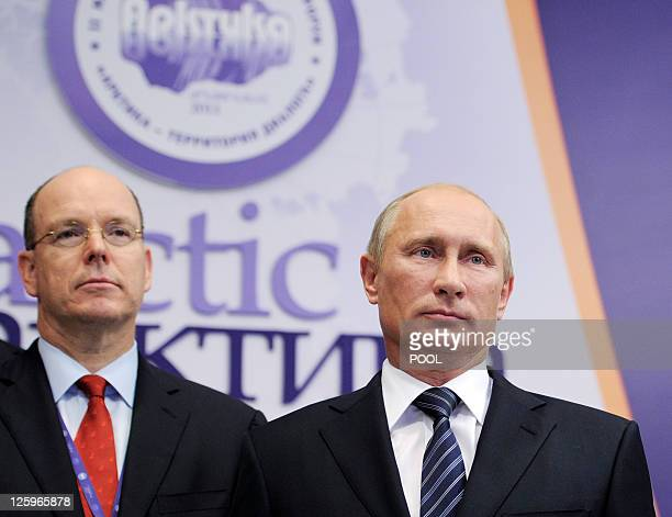 Russia's Prime Minister Vladimir Putin stands next to Albert II Sovereign Prince of Monaco as they attend the plenary meeting of the Second...