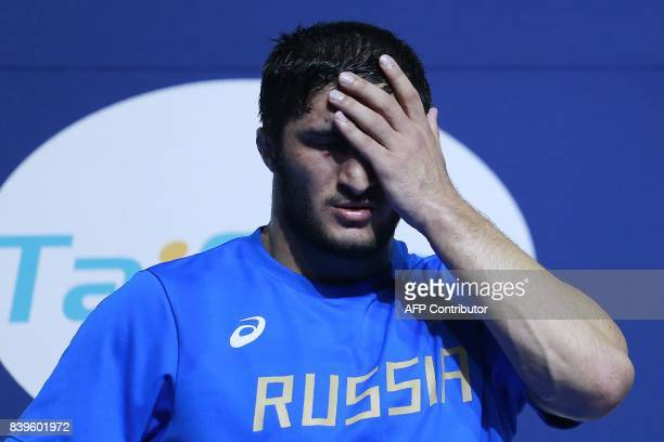 Russia's silver medallist Abdulrashid Sadulaev reacts on the podium during the medal ceremony for the men's freestyle wrestling 97kg category at the...