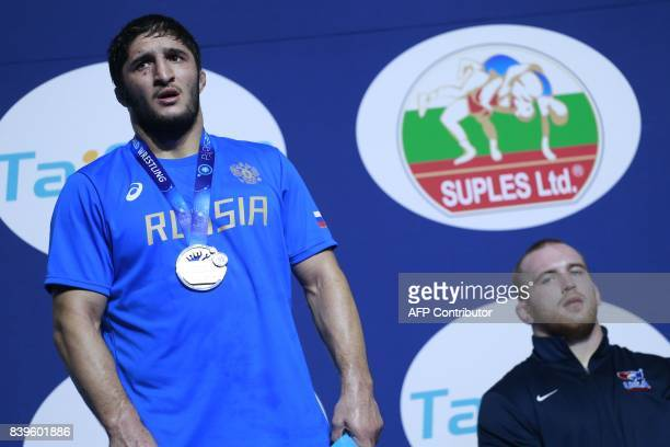 Russia's silver medallists Abdulrashid Sadulaev poses on the podium next to USA's gold medallist Kyle Snyder during the medal ceremony for the men's...