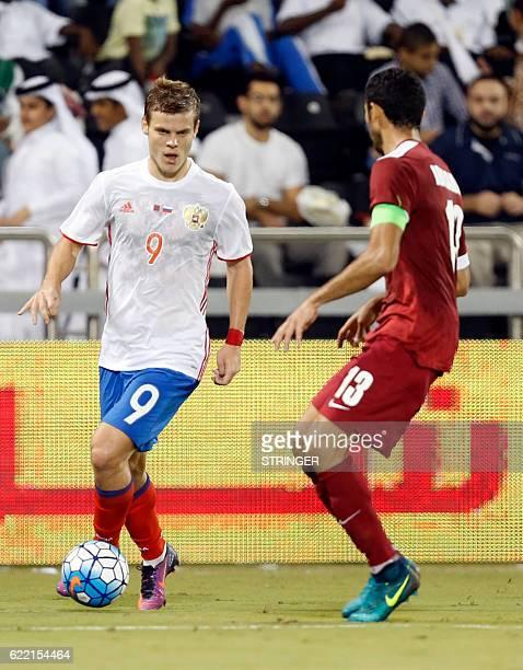 Russia's striker Aleksandr Kokorin is marked by Qatar's defender Ibrahim Majid during the International friendly match between Qatar and Russia at...