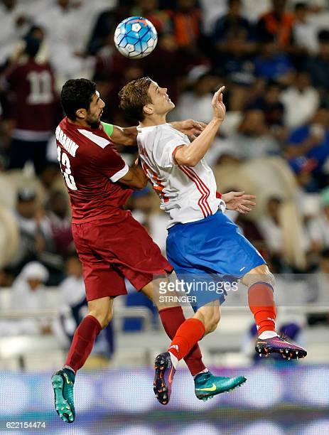 Russia's striker Aleksandr Kokorin vies for the header with Qatar's defender Ibrahim Majid during the International friendly match between Qatar and...