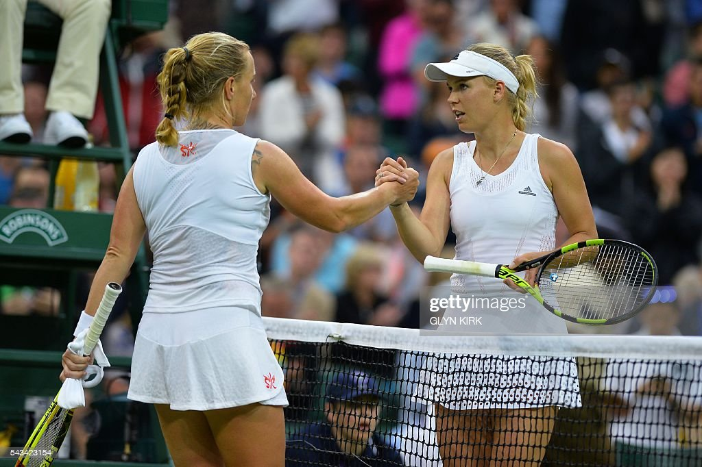 Russia's Svetlana Kuznetsova (L) shakes hands with Denmark's Caroline Wozniacki (R) after Kuznetsova won their women's singles first round match on the second day of the 2016 Wimbledon Championships at The All England Lawn Tennis Club in Wimbledon, southwest London, on June 28, 2016. / AFP / GLYN