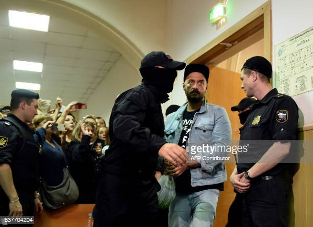 Russia's theatre and film director Kirill Serebrennikov charged with fraud is escorted by security officers ahead of a hearing at Moscow's Basmanny...