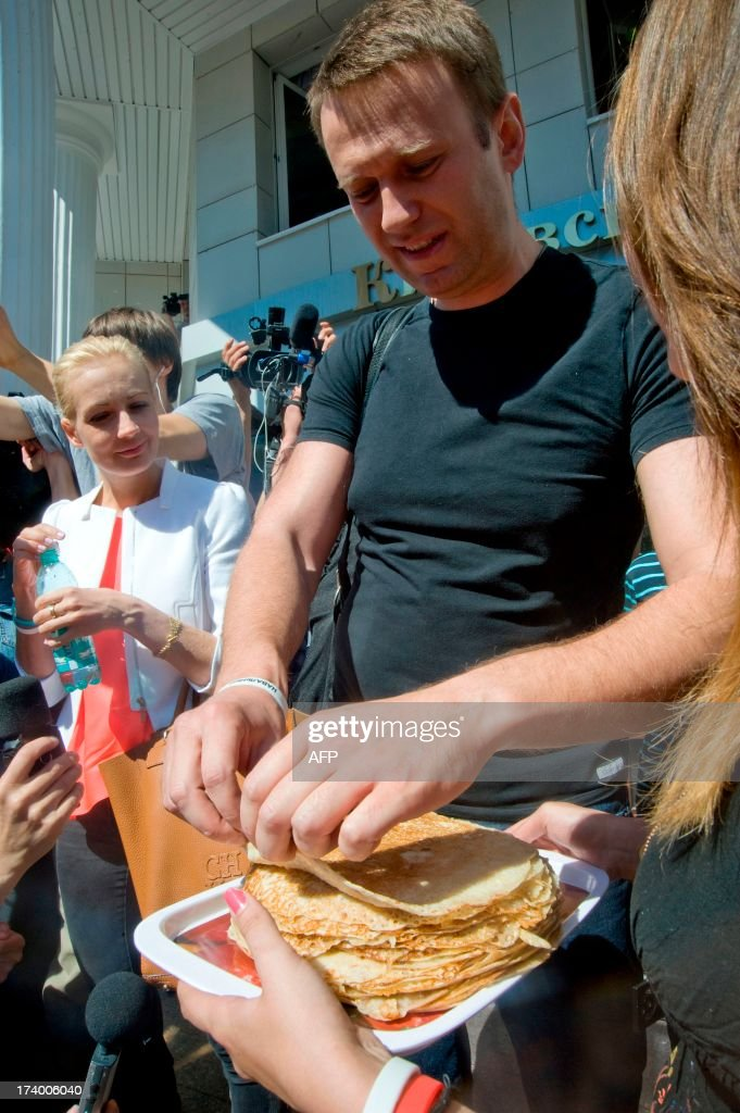 Russia's top opposition leader Alexei Navalny (R) and his wife Yulia eat a pancake after leaving the courtroom in Kirov on July 19, 2013. A Russian court on Friday unexpectedly freed protest leader Alexei Navalny pending his appeal against a five-year sentence on embezzlement charges, after his jailing prompted thousands to take to the streets in protest. The judge in the northern city of Kirov ruled that keeping President Vladimir Putin's top opponent in custody would deprive him of his right to stand in mayoral elections in Moscow on September 8. AFP PHOTO/SERGEI BROVKO
